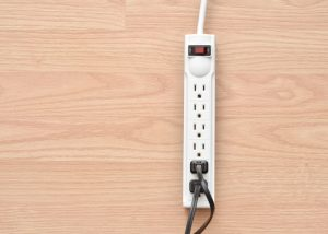 Closeup of a power bar with cords in it on a wood floor.